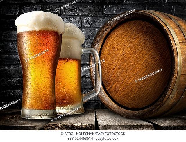 Wooden keg and beer near black brick wall