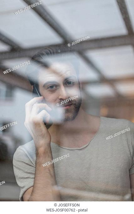Portrait of young man on the phone behind windowpane