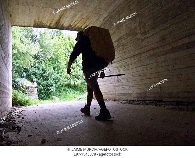 Silhouette of a hiker walking through highway underpass along the Camino de Santiago