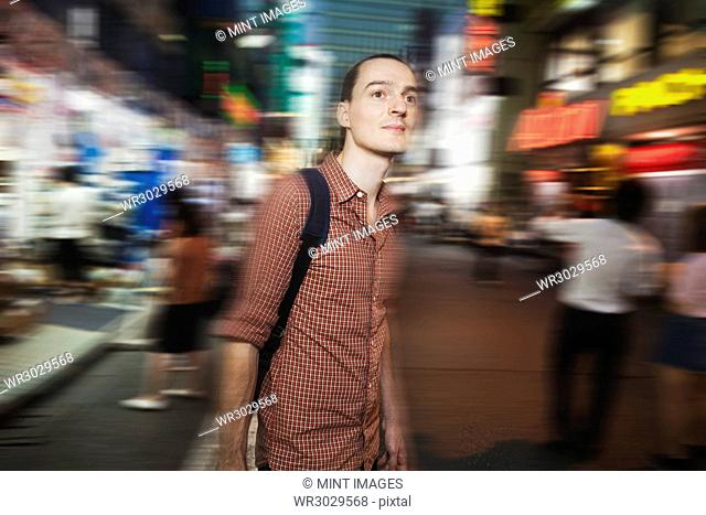 A western man on the street at night in Tokyo. A tourist in an urban environment, blurred motion
