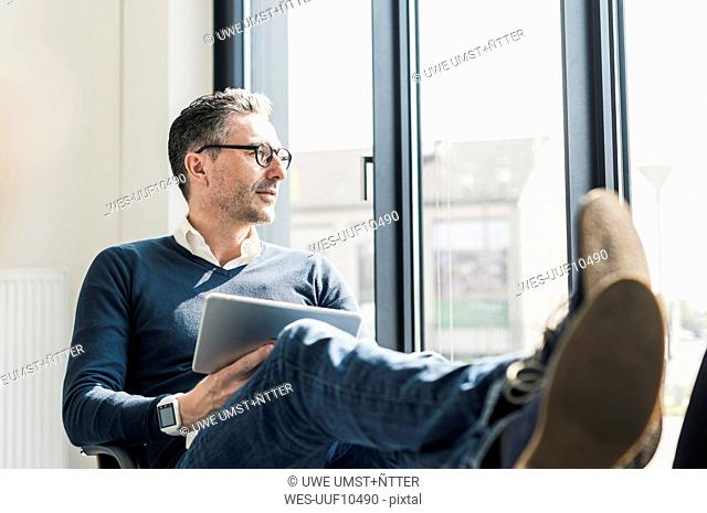 Businessman with tablet sitting with feet up in his office looking through window