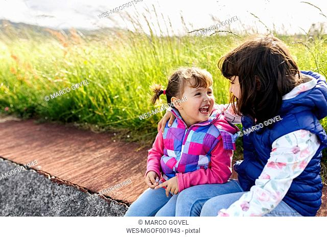 Two laughing little sisters sitting on curb beside a meadow