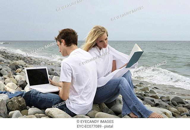 Portrait of young couple with book and laptop