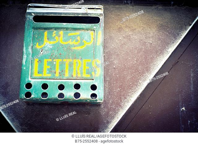 Green mailbox hanging on the door of a house, with text in french, lettres and in arab. Fez, Morocco, Africa