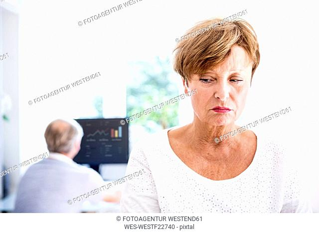 Serious senior woman with husband in background using computer