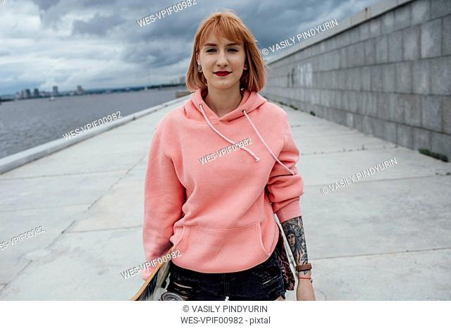 Portrait of young woman holding skateboard at the riverside