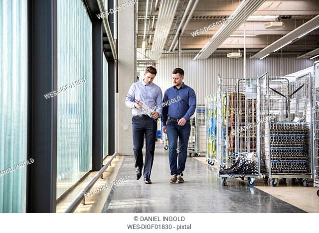 Two men walking in factory shop floor talking about product