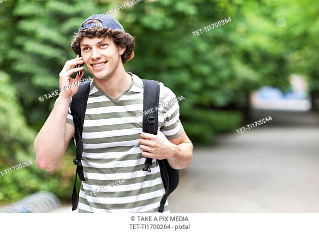 Male college student talking on cell phone