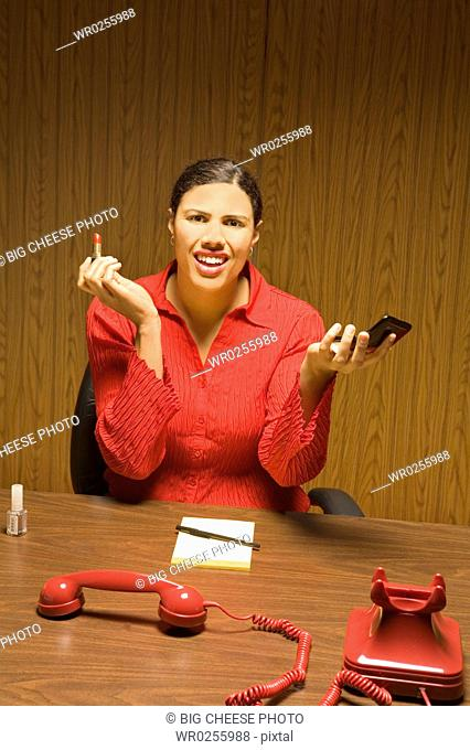 Businesswoman applying lipstick with telephone off the hook