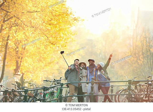 Playful young friends taking selfie with selfie stick on urban autumn bridge, Amsterdam