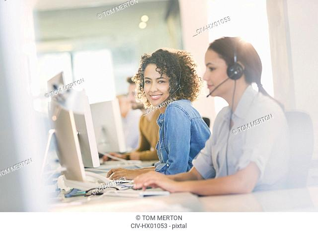 Portrait smiling businesswoman with headset working at computer in office