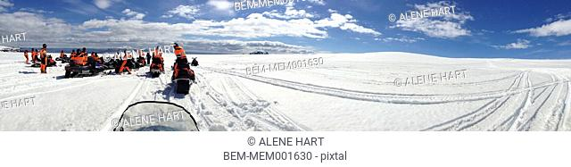 Panoramic view of people on snow mobiles in snowy landscape