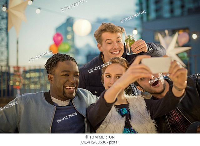 Young adult friends taking selfie at rooftop party