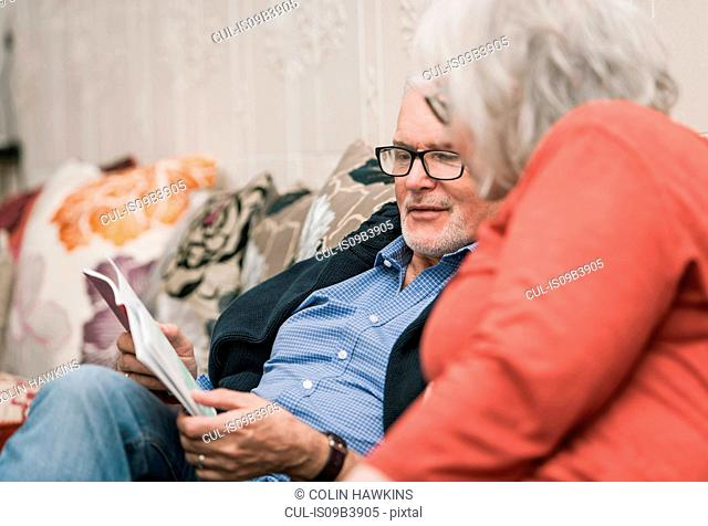 Senior couple reading book on couch