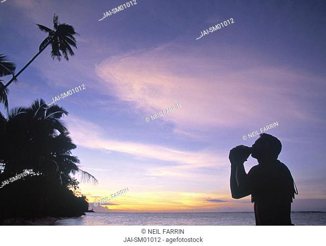Man blowing inro a seashell, Samoa