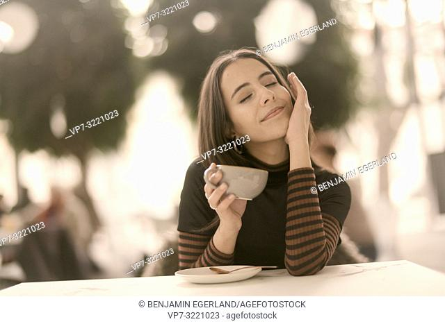 portrait of pleased woman holding coffee cup while enjoying break at table in café, closed eyes, pure joy, in Munich, Germany