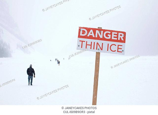 Danger sign and people on frozen Lake Louise, Canada