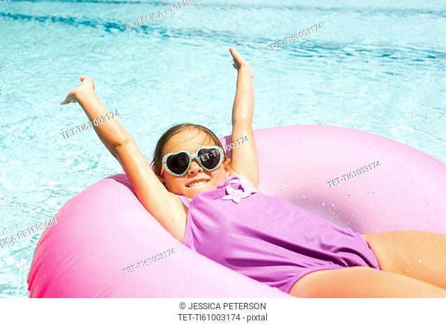 Smiling girl (4-5) relaxing in inflatable ring
