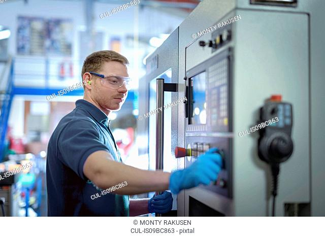 Engineer operating milling machine in precision engineering factory