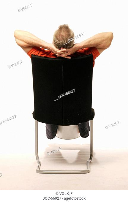 back view of an older man sitting on a chair - holding a waste paper basket between his lower legs - his arms are folded behind his neck
