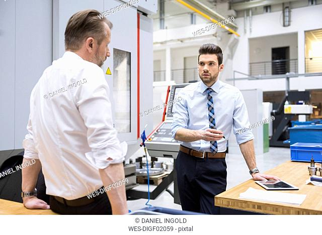 Two businessmen at table in factory shop floor discussing