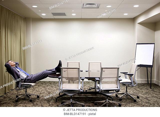 Caucasian businessman putting feet up in conference room