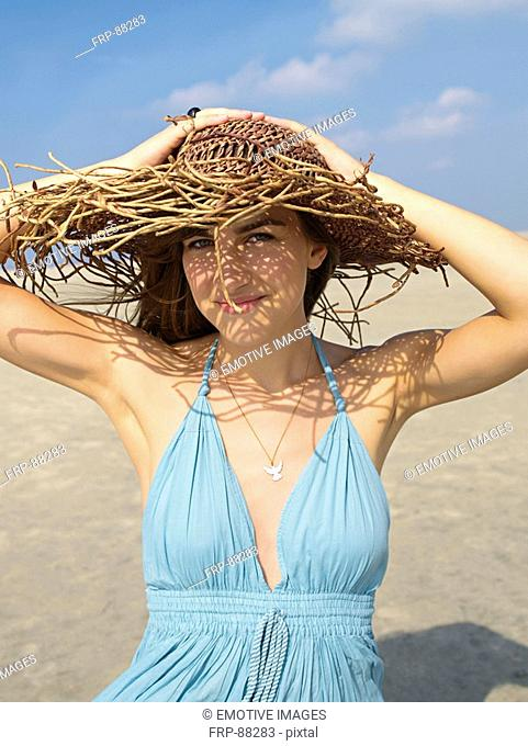 Young woman in a summerdress and with hat