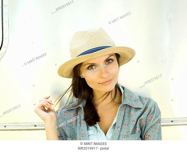 A young woman in a straw hat, her head tilted looking curious