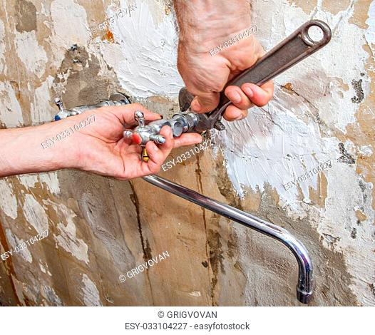 Dismantling of old faulty faucet, close-up hands of plumber with adjustable wrench