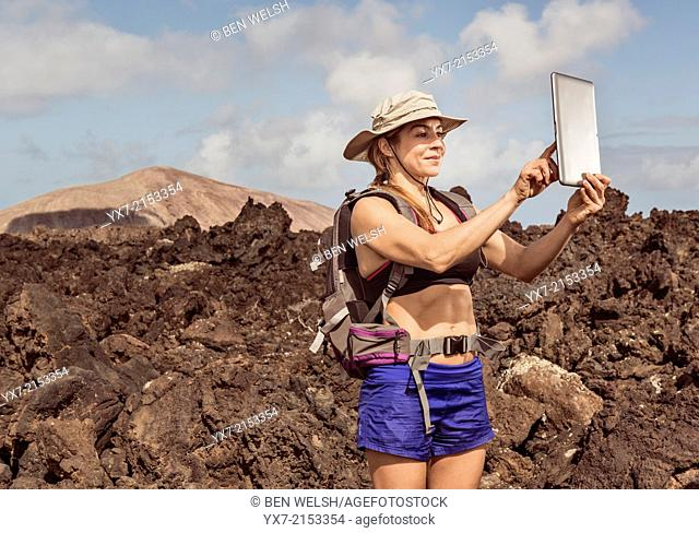 Traveler using a tablet at Timanfaya National Park, Lanzarote, Canary Islands, Spain