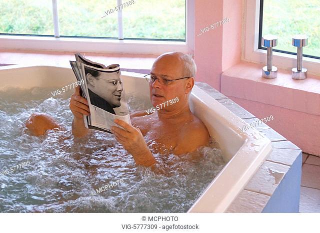 Ein aelterer mann sitzt im Whirlpool und liest ein Magazin 2006 - Schleswig-Holstein, Germany, 01/12/2006