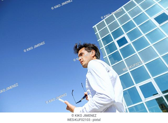 Businessman with tablet and sunglasses outside office building