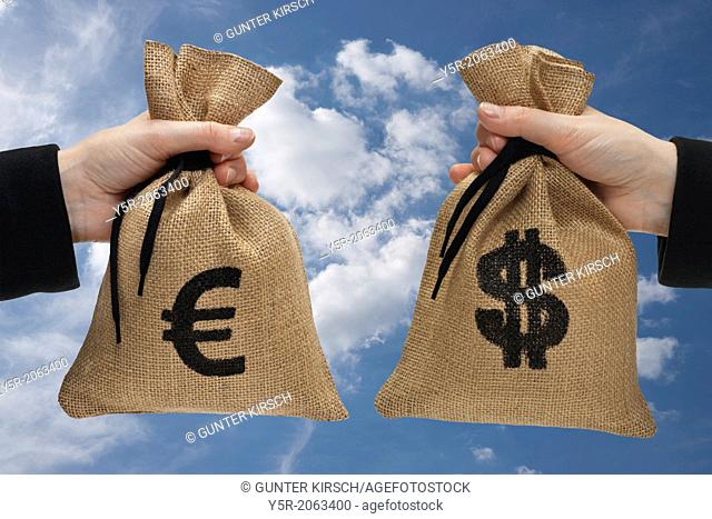 A money bag with euro sign and a money bag with dollar sign are hand-held