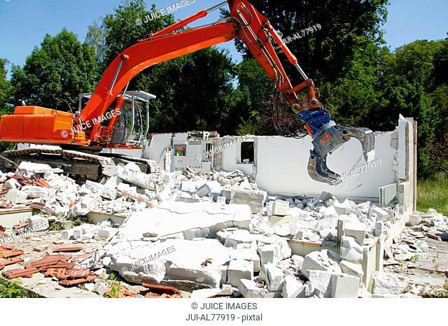 Machine demolishing home