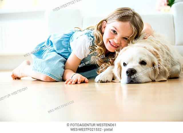 Little girl cuddling with her dog, lying on floor