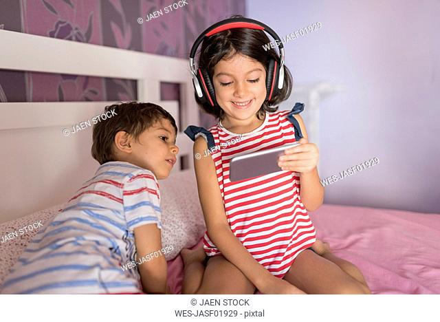 Little boy and his older sister sitting on bed at home looking at smartphone