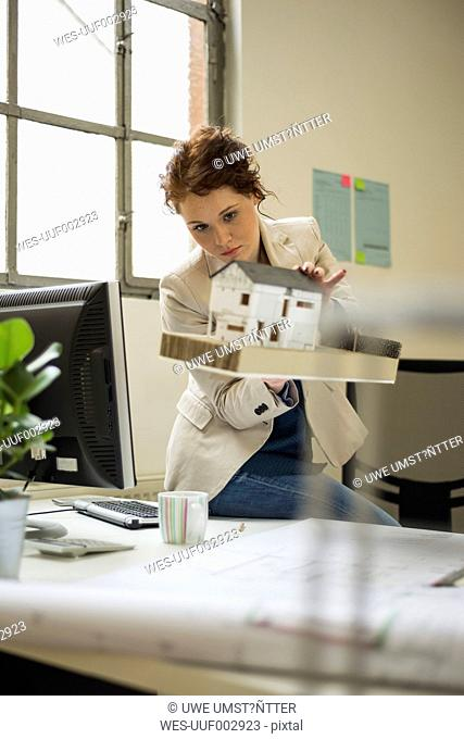 Young woman in office with architectural model