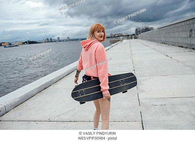 Young woman holding skateboard walking at the riverside