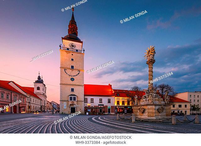 Trnava, Slovakia - April 9, 2019: City tower and Holy Trinity Statue in the main square of Trnava, Slovakia