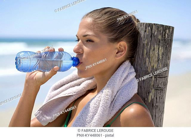 Woman leaning against a wooden post on the beach drinking water