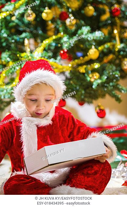 Surprised boy opens a Christmas gift, Christmas tree and gifts on background