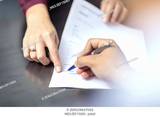 Close-up of signing a document