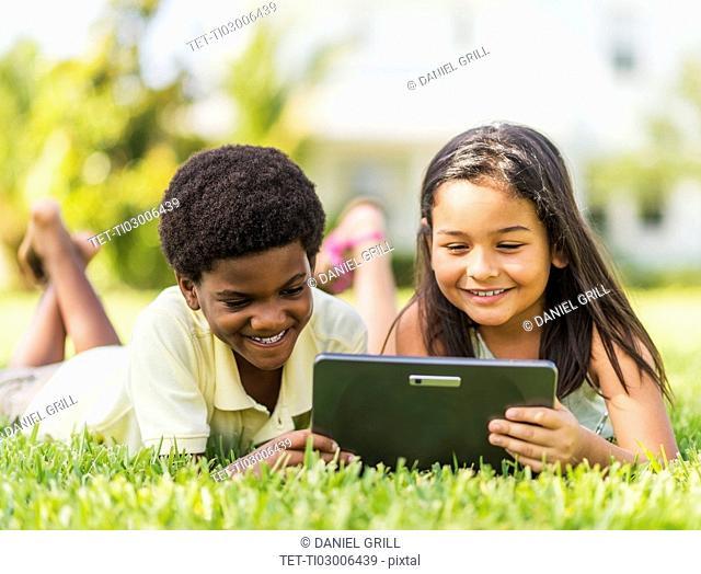 girl ( 8-9) and boy (6-7) using digital tablet