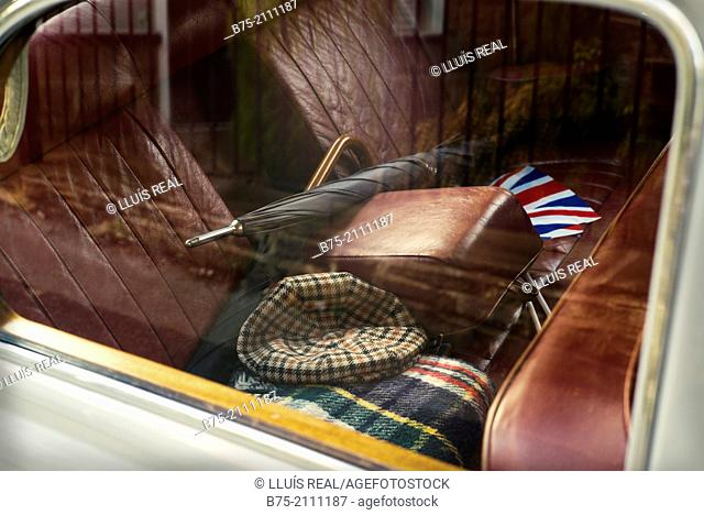 Foreground inside an antique car brand Rover with red leather upholstery with two umbrelas, hat, car blanquet and an english flag in England, UK, Europe