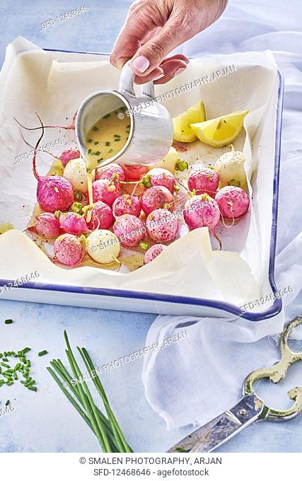 Pouring sauce on Roasted Radishes, lemon, olive oil, chive, mustard, white wine vinegar in oven dish