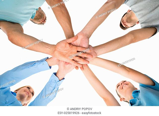 Low Angle View Of People Hands Stacking Together Over White Background