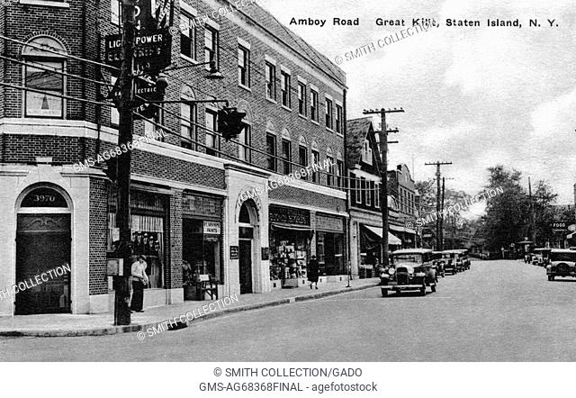 Postcard with early 20th century cars in street, shops, and sign behind telephone pole that appears to be 'Light, Power Gas Electric', titled 'Amboy Road