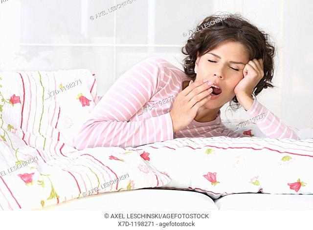 brunette woman in bed yawning