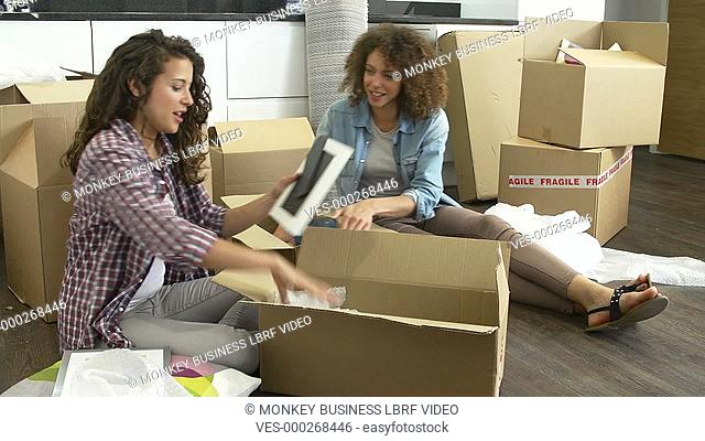 Two women packing breakables into cardboard box ready for move. Shot on Sony FS700 in PAL format at a frame rate of 25fps