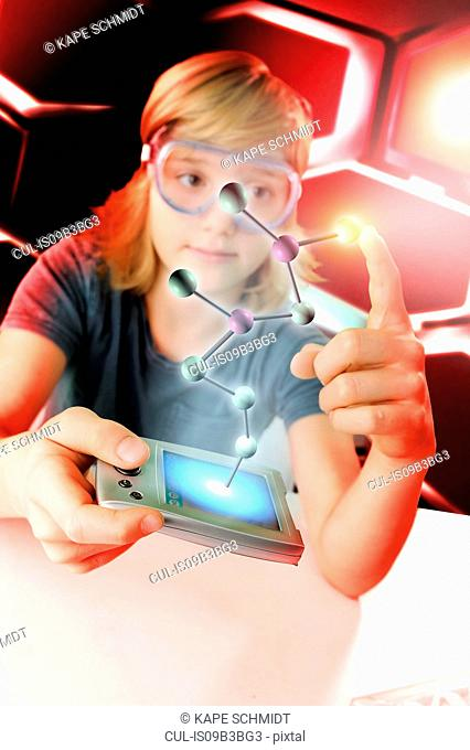 Boy with hand held computer touching 3D molecular model
